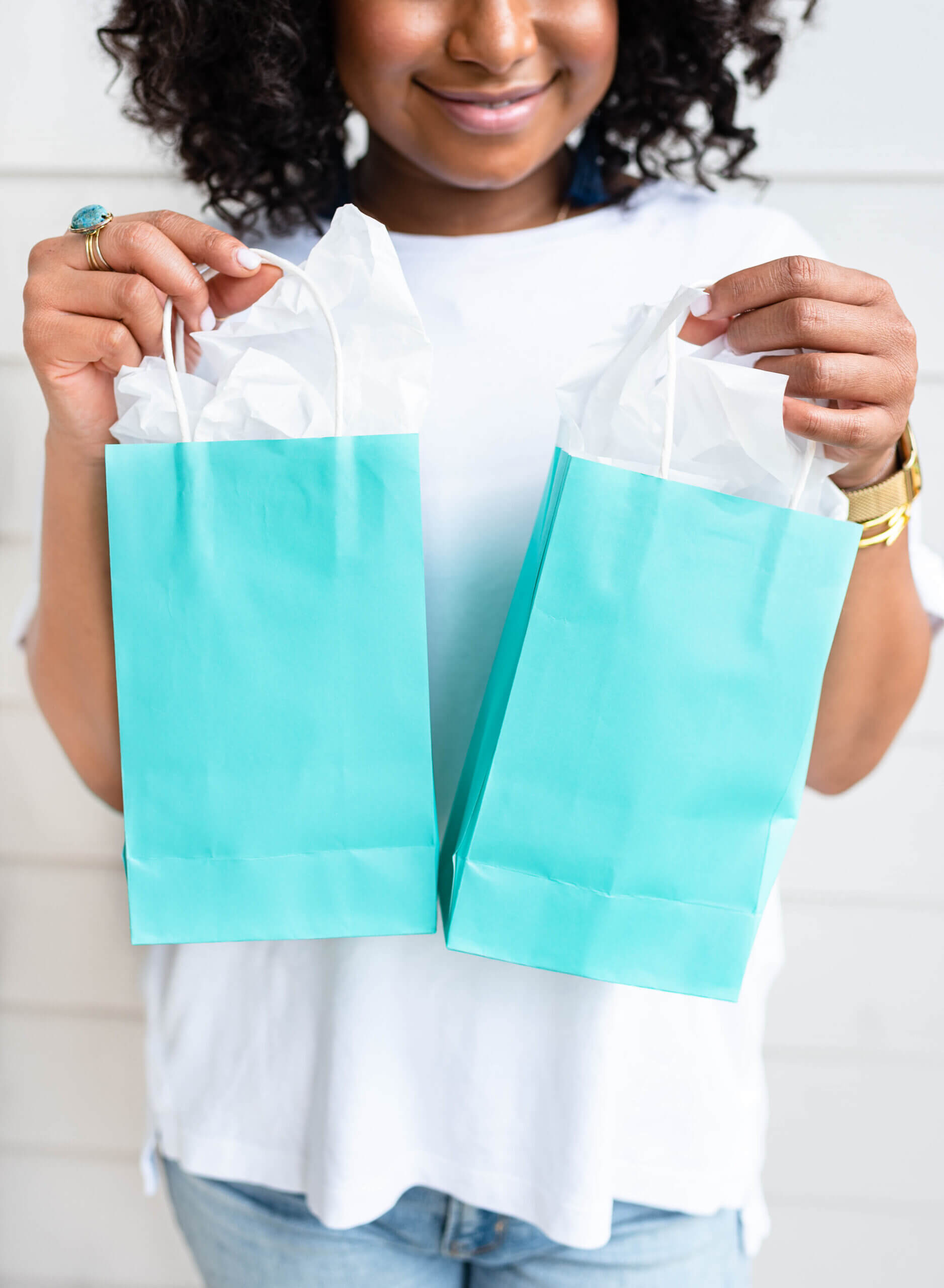 Woman smiling, holding two cyan shopping bags