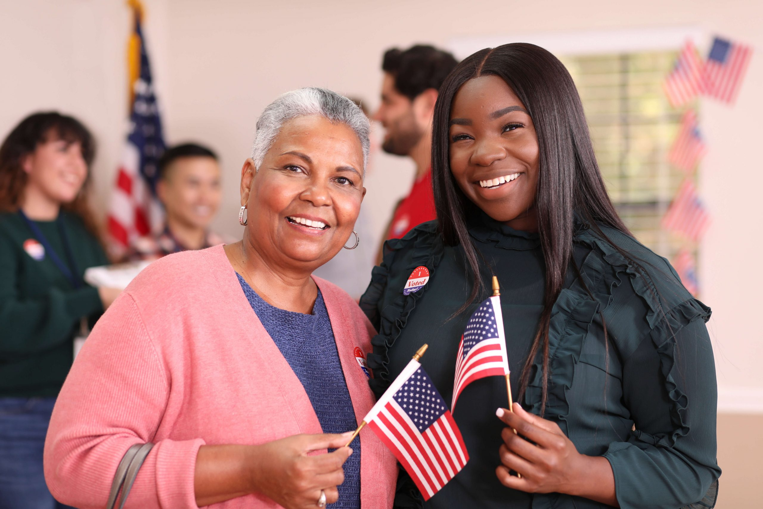 Two women at polling place, smiling, holding American flags
