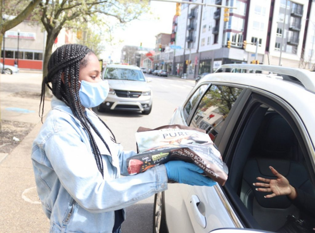 Woman in mask and gloves handing dog food woman in car