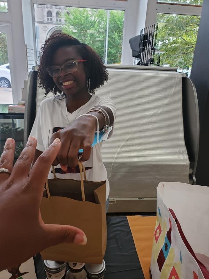 Catapult Kids graduate Jillian Lavender-Kalon Beauty hands a shopping bag to a customer while smiling