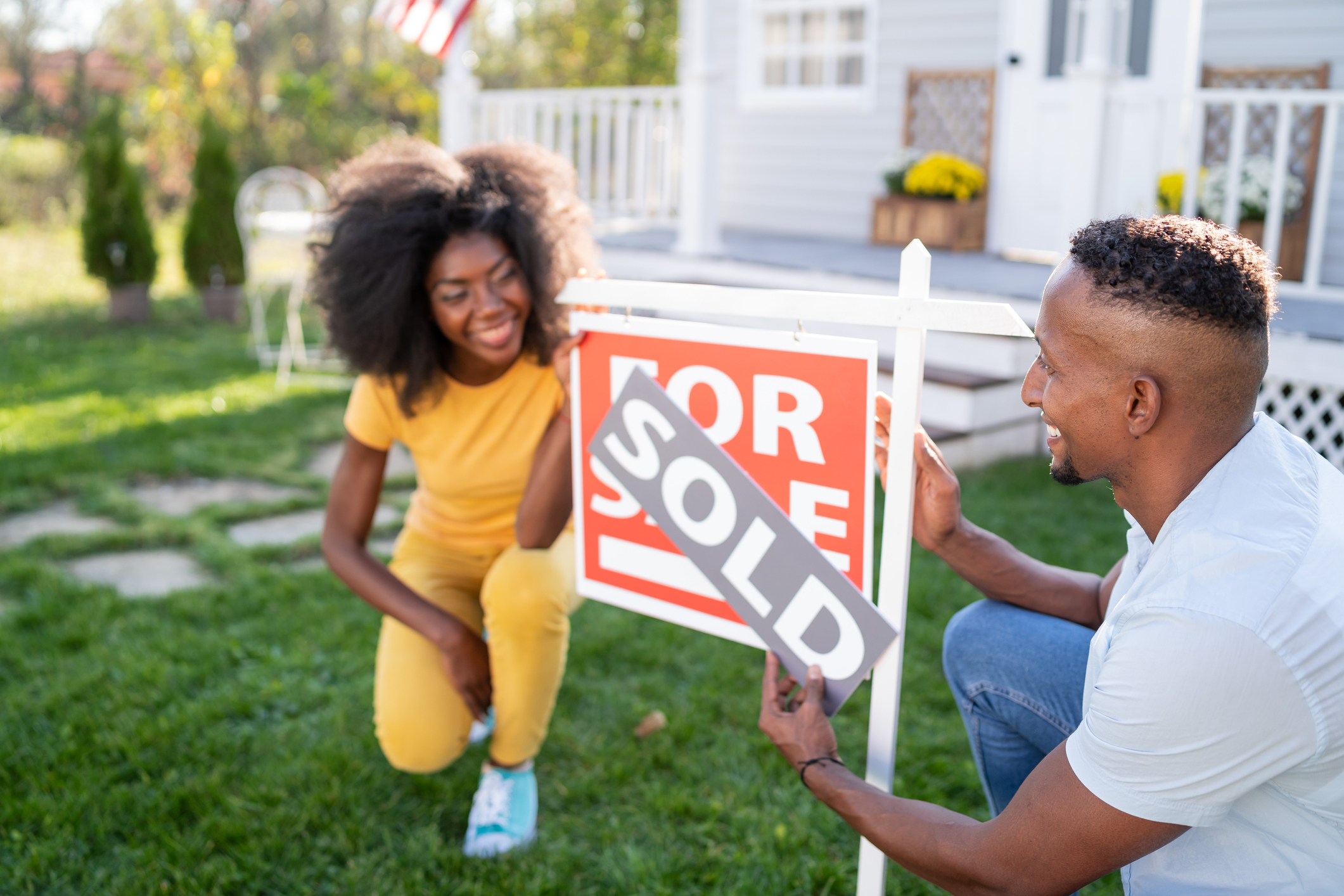 """A black couple crouch outside a newly-purchased home. The female partner at the left, on one knee, watches, smiling, as the male partner on the right places a """"sold"""" decal over the """"for sale"""" sign in the lawn."""
